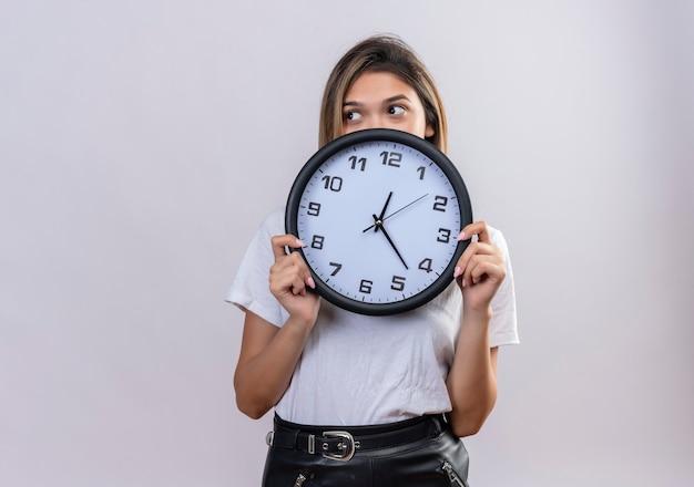 Urocza młoda kobieta w białej koszulce trzyma zegar ścienny, patrząc z boku na białą ścianę