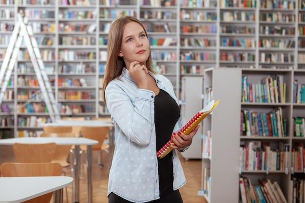 Urocza młoda kobieta w bibliotece lub księgarni