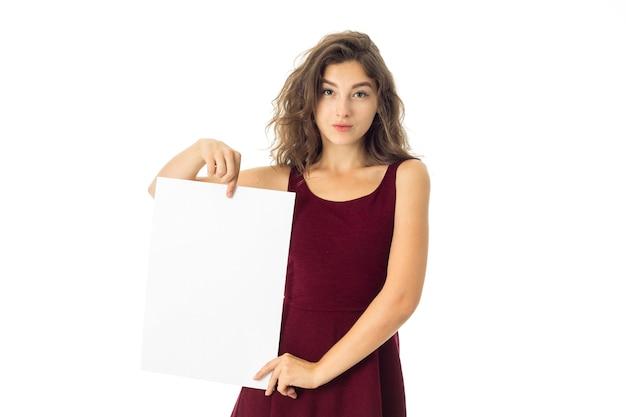 Urocza młoda kobieta w czerwonej sukience z białą tabliczką w rękach na białym tle
