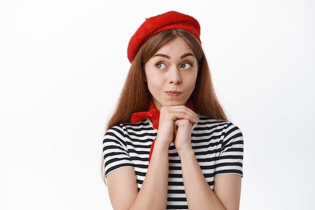 Urocza młoda kobieta w czerwonym berecie i szaliku, patrząca na bok z zamyśloną słodką twarzą, myśląca lub śniąca, stojąca nad białą ścianą