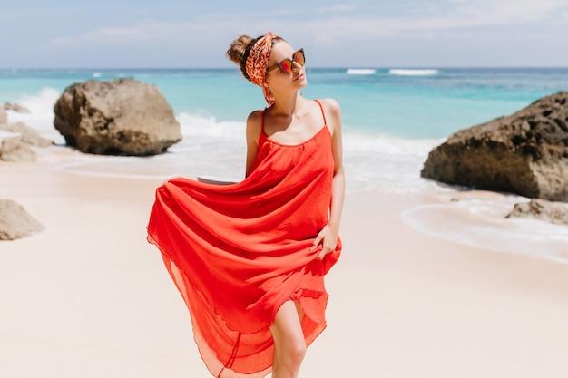 Urocza młoda kobieta w długiej czerwonej sukience pozowanie na dzikiej plaży ze skałami. odkryty strzał zgrabnej dziewczyny idącej w pobliżu morza.