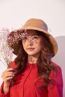 Urocza młoda kobieta w letniej sukience i słomkowym kapeluszu pozowanie, trzymając bukiet kwiatów