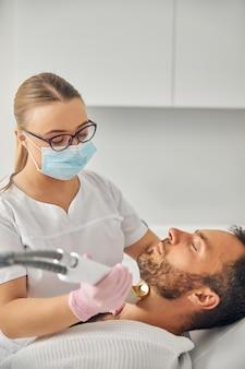 Urocza młoda kobieta w medycznej masce na twarz usuwająca niechciane włosy z męskiej szyi za pomocą urządzenia laserowego
