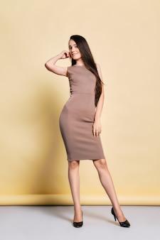 Urocza młoda kobieta w obcisłej sukience z dzianiny, długie proste, czarne włosy i buty na wysokim obcasie pozowanie w studio