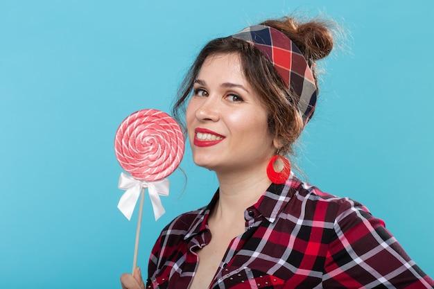 Urocza młoda kobieta w strojach retro, trzymając w dłoniach kolorowe lizaki i lizanie jednego pozowanie