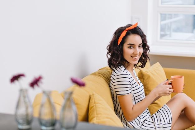 Urocza młoda kobieta w sukni, uśmiechając się na kanapie w nowoczesnym mieszkaniu. pomarańczowe, białe, złote kolory, wesoły nastrój, uśmiechnięty, odpoczywający, relaksujący