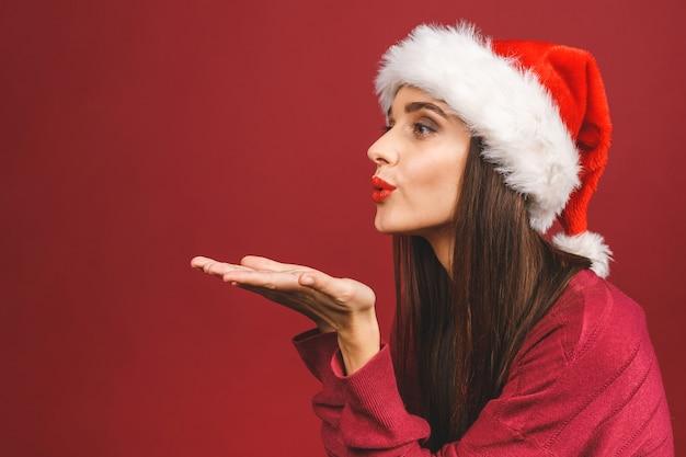 Urocza młoda kobieta w świątecznym swetrze i czapce mikołaja, przesyła buziaka