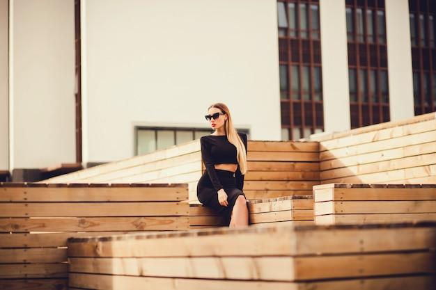 Urocza młoda kobieta w szkłach siedzi w mieście