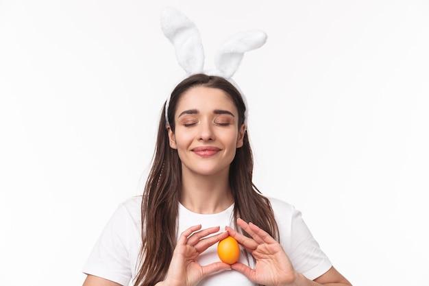 Urocza młoda kobieta w uszach królika, trzymając kolorowe jajko