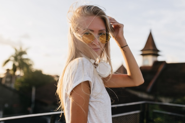 Urocza młoda kobieta w żółte okulary pozowanie na tle nieba.