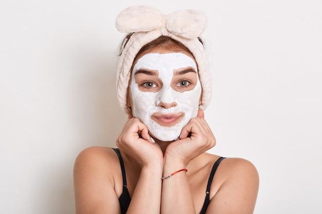 Urocza młoda kobieta z białą maseczką na twarz, dziewczyna z opaską na włosy robi zabieg kosmetyczny
