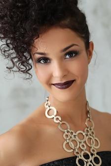 Urocza młoda kobieta z czarnymi kręconymi włosami i czarną błyszczącą sukienką