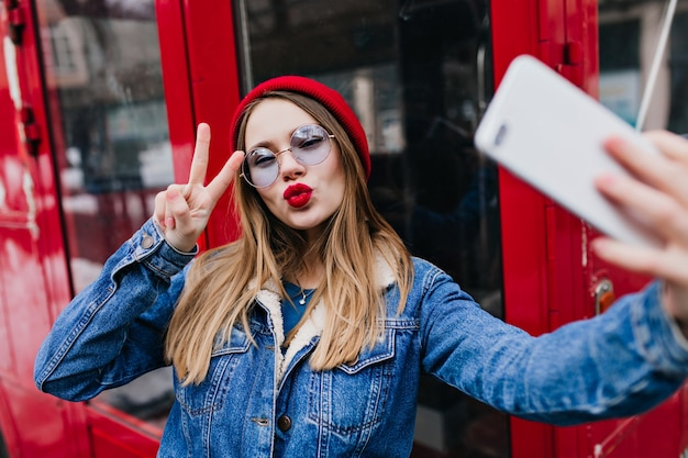 Urocza młoda kobieta z czerwonymi ustami dokonywanie selfie w dzień wiosny i przy użyciu telefonu.