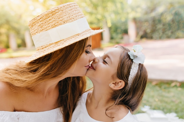 Urocza młoda kobieta z długimi czarnymi rzęsami całuje z miłością swoją uśmiechniętą córkę. close-up portret uroczej mamy i słodkie długowłose dziecko kobiece ze wstążką.