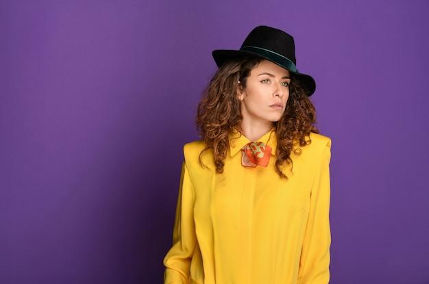 Urocza młoda kobieta z długimi kręconymi kasztanowymi włosami w stylu lat 80., ubrana w kapelusz fedora, jasnożółty top i chustkę na szyi, patrzącą w bok na fioletowym tle