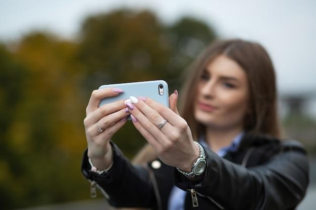 Urocza młoda kobieta z długimi włosami uśmiecha się i robi autoportret na telefonie komórkowym w parku