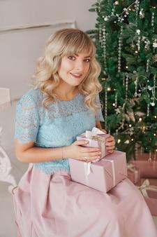Urocza młoda kobieta z eleganckim stylem siedząca wewnątrz w pobliżu udekorowanego drzewa z różowymi prezentami świątecznymi