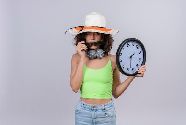 Urocza młoda kobieta z krótkimi włosami w zielonej krótkiej bluzce w kapeluszu przeciwsłonecznym, trzyma zegar ścienny i patrzy przez okulary przeciwsłoneczne na białym tle
