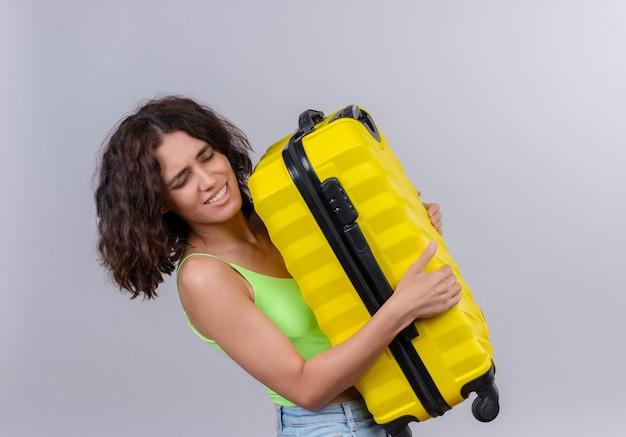 Urocza młoda kobieta z krótkimi włosami w zielonym crop topie, niosąca ciężką żółtą walizkę na białym tle