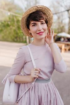 Urocza młoda kobieta z lśniącymi krótkimi włosami pozuje z przyjemnością podczas spaceru w parku