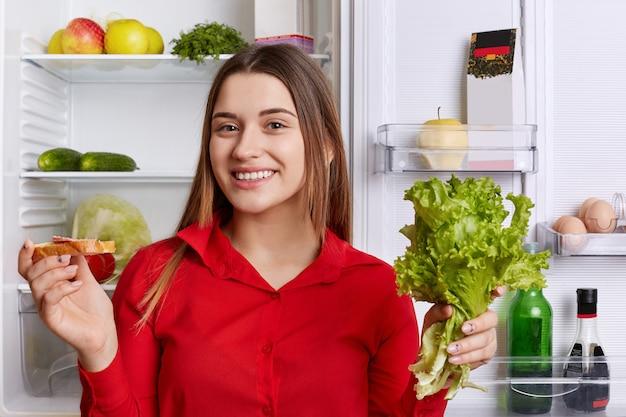 Urocza młoda kobieta z radosnym wyrazem twarzy, ubrana w czerwoną bluzkę, trzyma sałatę i kanapkę, stojąc w kuchni przy otwartej lodówce i przygotowując pyszne śniadanie. pozytywność i szczęście