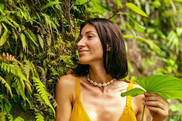 Urocza młoda kobieta z uśmiechem na twarzy, podziwiając tropikalną przyrodę zdjęcie stockowe stock