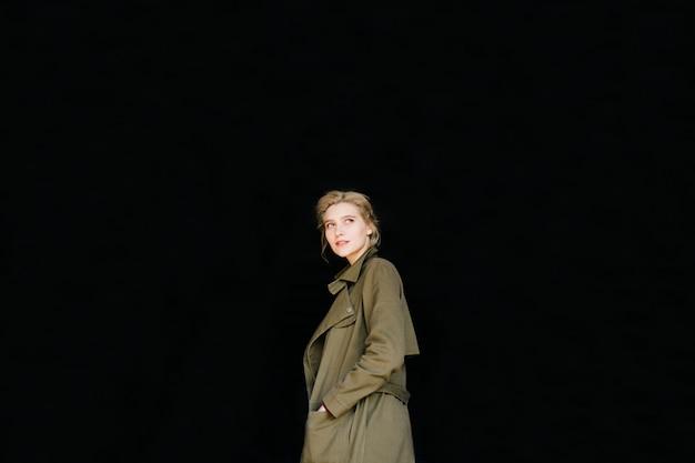 Urocza młoda kobieta z zielonym płaszczem