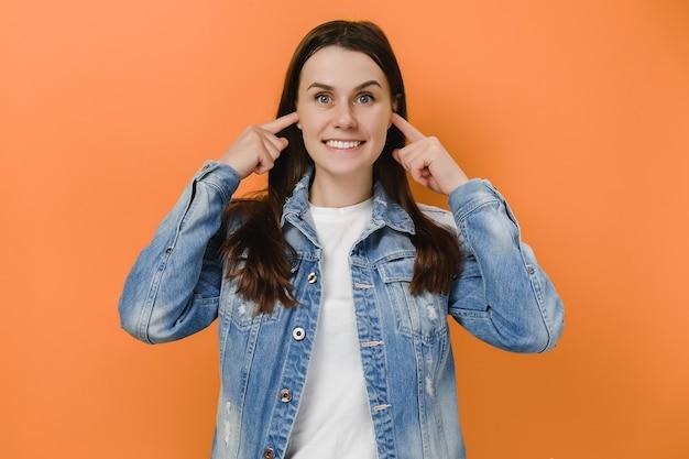 Urocza młoda kobieta zatyka uszy przyjemnie się uśmiecha
