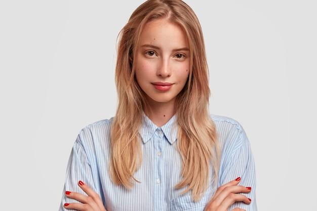 Urocza młoda kobieta ze skrzyżowanymi rękami, poważnie patrzy na aparat, ma pewny wyraz twarzy, odizolowane na białej ścianie