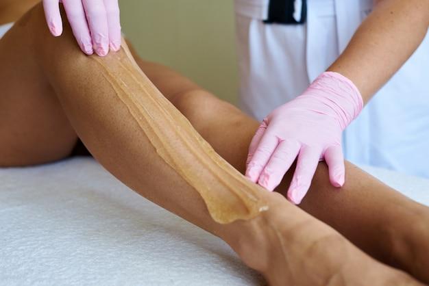 Urocza młoda kosmetyczka nakłada pastę cukrową na nogę klientki. depilacja z shugaringiem. kosmetyczka depilująca młoda kobieta.