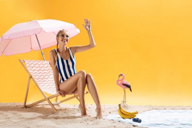 Urocza młoda modelka w pasiastym stroju kąpielowym uśmiecha się i odwraca wzrok