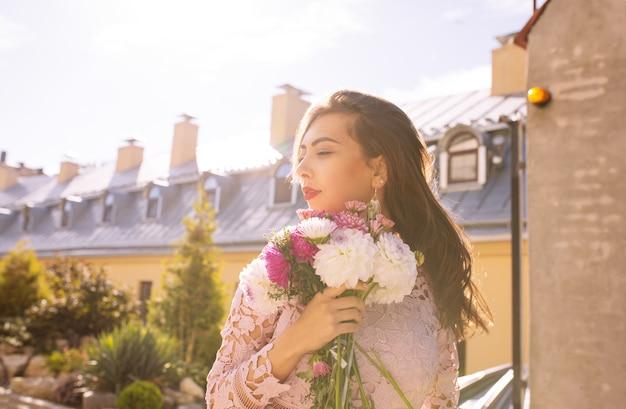 Urocza młoda modelka w różowej sukience z kwiatami w rękach na tle miasta