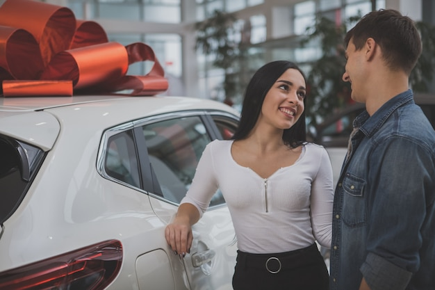 Urocza młoda para małżeńska kupuje razem nowy samochód