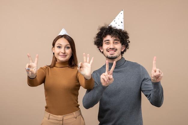 Urocza młoda para nosi kapelusz noworoczny dziewczyna pokazując pięć facet pokazujący trzy na szaro