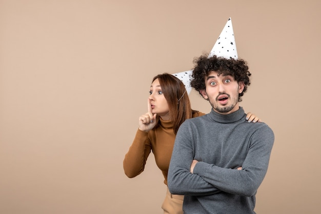 Urocza młoda para nosi kapelusz noworoczny dziewczyna robi gest ciszy komuś stojącemu za facetem na szaro