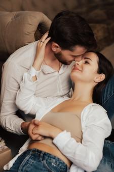 Urocza młoda para przytulanie, uśmiechanie się i patrzenie na siebie.