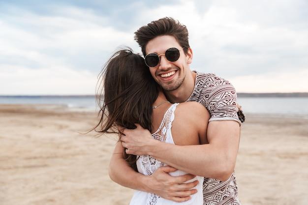 Urocza młoda para spędzająca zabawny czas na plaży, przytulająca się