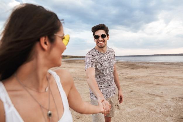 Urocza młoda para spędzająca zabawny czas na plaży, trzymając się za ręce