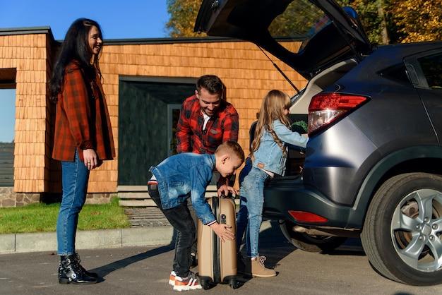 Urocza młoda rodzina ładująca samochód