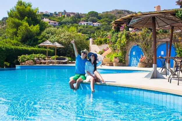 Urocza młoda romantyczna para relaksuje przy basenem