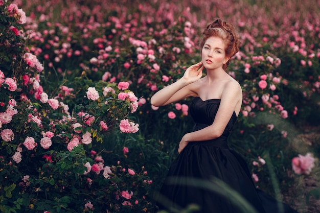 Urocza młoda rudowłosa kobieta w czarnej sukience w ogrodzie różanym.