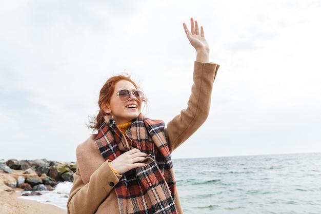 Urocza młoda rudowłosa kobieta w jesiennym płaszczu spacerująca po plaży, machająca ręką