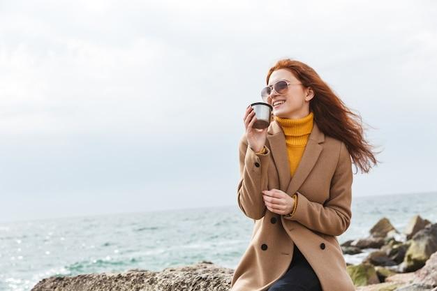 Urocza młoda rudowłosa kobieta w jesiennym płaszczu spacerująca po plaży, pijąca gorącą kawę z termosu