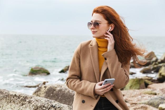 Urocza młoda rudowłosa kobieta w jesiennym płaszczu spacerująca po plaży, słuchająca muzyki przez słuchawki
