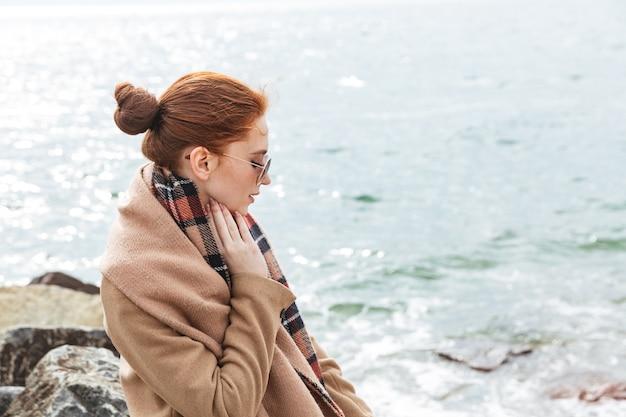 Urocza młoda rudowłosa kobieta w jesiennym płaszczu spacerująca po plaży