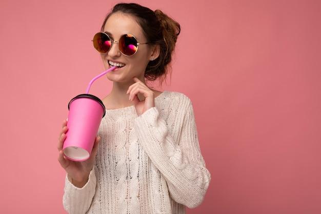 Urocza młoda szczęśliwa brunetka kobieta nosi stylowe ubrania odizolowane na kolorowej ścianie w tle