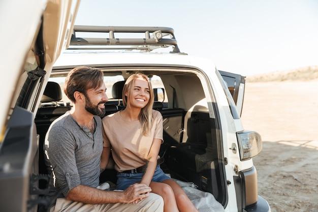 Urocza młoda szczęśliwa para siedzi z tyłu samochodu na plaży, obejmując