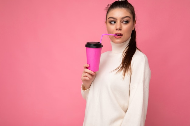 Urocza młoda szczęśliwa szczęśliwa brunetka kobieta nosi stylowe ubrania na białym tle nad kolorowe tło ściany trzymając papierowy kubek do makiety do picia koktajl mleczny, patrząc z boku. kopiuj przestrzeń
