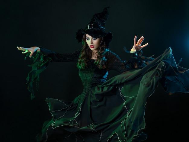 Urocza młoda wiedźma w kostiumie wykonuje magiczne kroki dwiema rękami