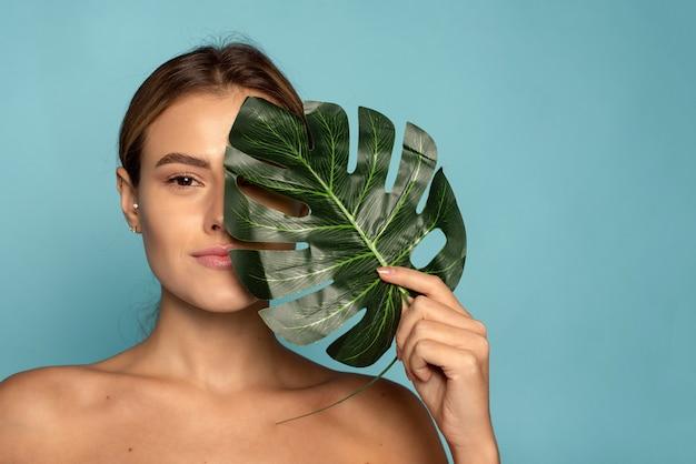 Urocza modelka zakrywa część twarzy tropikalnym liściem palmowym. pielęgnacja skóry, nawilżenie. kosmetyki z naturalnymi składnikami.